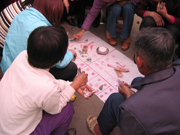 路上にて、サイコロを使った賭け事「大小」に興じる人々